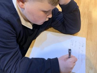 Kaiden Wilson writing a diary entry for his schoolwork